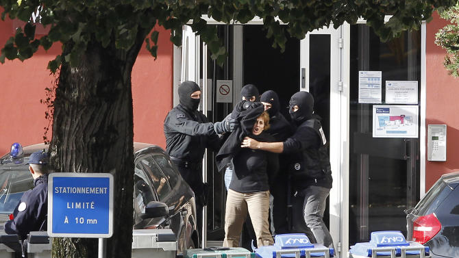 "Izaskun Lesaka, center, surrounded by French Police officers, reacts as she leaves the hotel where she was arrested in the early hours of Sunday with another as yet unnamed suspected member of ETA, in Macon, central eastern France, Sunday, Oct. 28, 2012. French police have arrested a top leader of the Basque separatist group ETA in eastern France, the Spanish interior ministry said in a statement on Sunday. Izaskun Lesaka, one of ""the three main leaders"" of the banned organisation, was arrested during a raid by an elite French police unit at a hotel in the town of Macon, near the city of Lyon, it said. (AP Photo/Laurent Cipriani)"