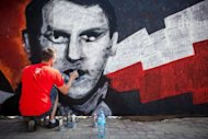 A street artist works on a mural as he takes part in a 'Graffiti Jam' to commemorate Polish resistance artists, musicians, film makers and writers who fought during the 'Warsaw Uprising' in World War II, on July 28, 2012