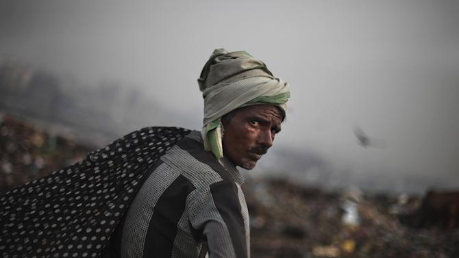 In this Sept. 13, 2012 photograph, an Indian ragpicker pauses for a while as he goes about the routine of searching through garbage for reusable garbage at a dumping ground on the outskirts of New Delhi, India. Those whose survival depends on this gray market in trash fear their lives are about to be upended. Because where they see money in those mountains of garbage, the New Delhi government sees electricity. Desperate for cheap energy, the Delhi government is experimenting with power plants fueled by garbage. One plant is now running on a trial basis and two more are under construction. (AP Photo/Altaf Qadri)