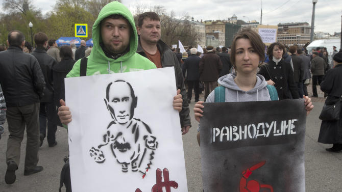 Demonstrators holds posters showing a cartoon mocking Russian President Vladiimir Putin, at left, and another reading Indifference and showing a riot policeman, during an opposition rally in Moscow, Russia, Monday, May 6, 2013.  Up to 20,000 Russian opposition supporters gathered for a protest on Monday, venting anger against the Kremlin and demanding the release of political prisoners. The protest came exactly one year after a demonstration a day before President Vladimir Putin's third presidential inauguration on the same square near the Kremlin ended in violent clashes between demonstrators and police. (AP Photo/Misha Japaridze)