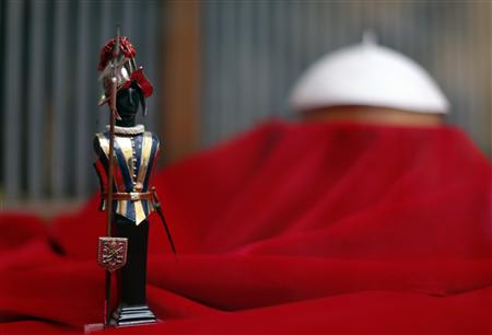 A model of a Swiss guard is seen next to a Papal white skull cap in the Gammarelli's tailor shop window in Rome