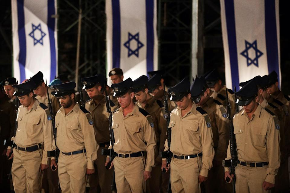 Israeli soldiers observe a minute of silence during a service marking Memorial Day at the Western Wall, the holiest site where Jews can pray, in Jerusalem's Old City, Tuesday, April 24, 2012. Israelis marked Memorial Day starting Tuesday evening in remembrance of the nation's fallen soldiers. (AP Photo/Bernat Armangue)