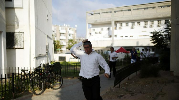 Ultra-Orthodox Jewish man runs for cover as a siren sounds, warning of incoming rockets in the southern city of Ashdod