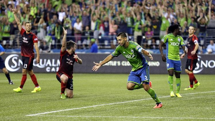 Seattle Sounders' Clint Dempsey, center, celebrates after scoring a goal against the Portland Timbers, in the second half of an MLS soccer match, Sunday, July 13, 2014, in Seattle. (AP Photo/Ted S. Warren)