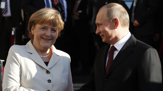 German Chancellor Angela Merkel welcomes Russian President Vladimir Putin for the opening of the Hannover Fair at the Congress Center in Hannover, Germany, Sunday April 7, 2013. (AP Photo/Frank Augstein)