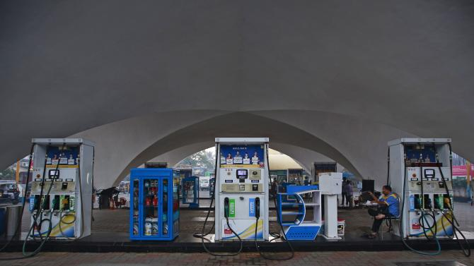 An employee of Bharat Petroleum sits next to a fuel pump at a fuel station in Mumbai
