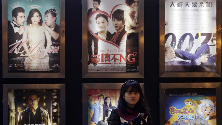 In this Wednesday Feb. 13, 2013 photo, a woman stands in front of the advertisements of Chinese and foreign films on showing at a movie theater in Shanghai, China. Tens of millions of film fanatics are entering theaters around Asia during the long Lunar New Year holiday, but Hollywood can't count on them to boost the box office for its mostly serious Oscar nominees. Even with the Academy Awards buzz at a peak barely two weeks before the ceremony, patrons are opting for lighter fare. (AP Photo/Eugene Hoshiko)