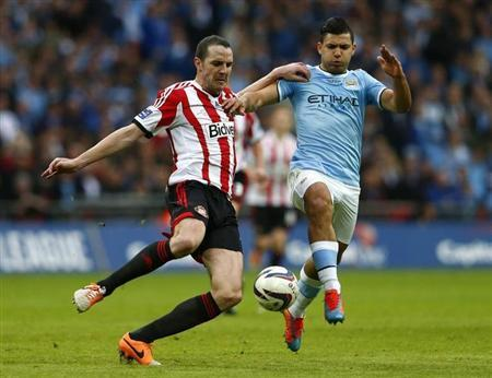 Manchester City's Aguero challenges Sunderland's O'Shea during their English League Cup final soccer match at Wembley Stadium in London