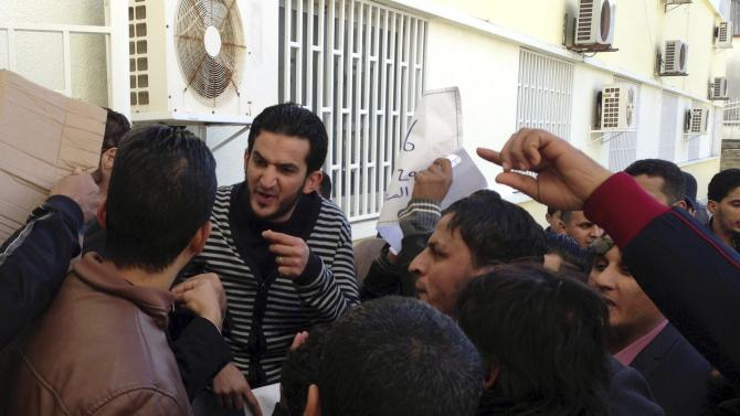 Staff member tries to prevent demonstrators from storming the headquarters of Libyan PM Thinni, in Bayda