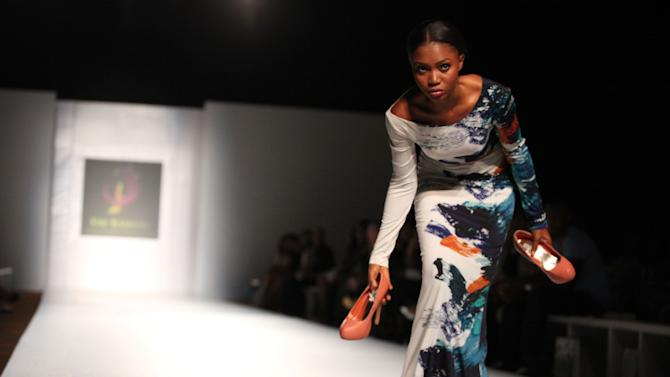 A model takes off her high heels after having trouble walking while modeling an outfit by designer Kiki Kamanu at the MTN Lagos Fashion and Design Week in Lagos, Nigeria, on Friday, Oct. 26, 2012. (AP Photo/Jon Gambrell)