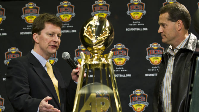 FILE - In this Jan. 11, 2011 file photo, Associated Press Sports Enterprise editor John Affleck, left, presents Auburn head coach Gene Chizik with the Associated Press National Championship trophy in Scottsdale, Ariz. Auburn beat Oregon 22-19 to capture the championship. (AP Photo/Morry Gash, File)