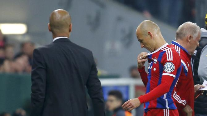Bayern Munich's Robben walks past coach Guardiola after being substituted during German Cup semi-final soccer match against Borussia Dortmund in Munich