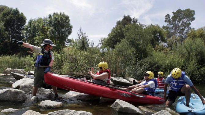 This Aug. 12, 2011 photo shows Ranger Tim Pera, left, with the Santa Monica Mountains Recreation Conservation Authority, helps other kayakers over a rocky area during a kayaking trip along the Los Angeles River.  For the first time ever a six week pilot program sponsored by the LA Conservation Corps will allow about 280 people to kayak one of the few stretches that actually look like a river in the Sepulveda basin. The effort was a decade in the making and required half a dozen local and federal agencies to sign off on the project.  (AP Photo/Noaki Schwartz)