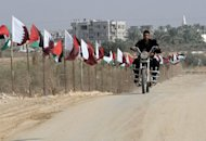 <p>A member of the Palestinian Hamas security forces rides a motorcycle past Palestinian and Qatari flags in Khan Yunis in the southern Gaza Strip on October 22. Qatari Emir Sheikh Hamad bin Khalifa al-Thani is set to arrive in the Gaza Strip on Tuesday in the first visit by a head of state since the Islamist Hamas movement took over in 2007.</p>