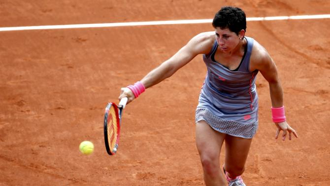 Carla Suarez Navarro of Spain plays a shot to Monica Niculescu of Romania during their women's singles match at the French Open tennis tournament at the Roland Garros stadium in Paris