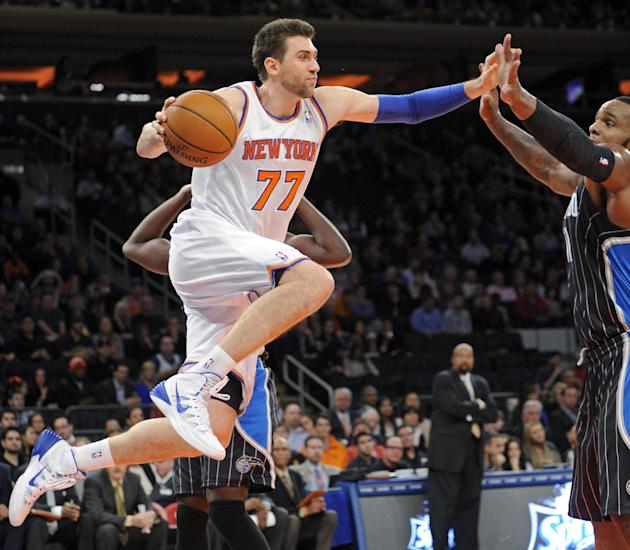 New York Knicks' Andrea Bargnani, left, drives under the basket as Orlando Magic center Glen Davis defends during the second quarter of an NBA basketball game on Friday, Dec. 6, 2013, at Madison S