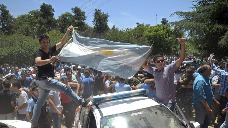 Policemen on strike stand on a police vehicle and display an Argentine flag as they celebrate reaching an agreement in Cordoba