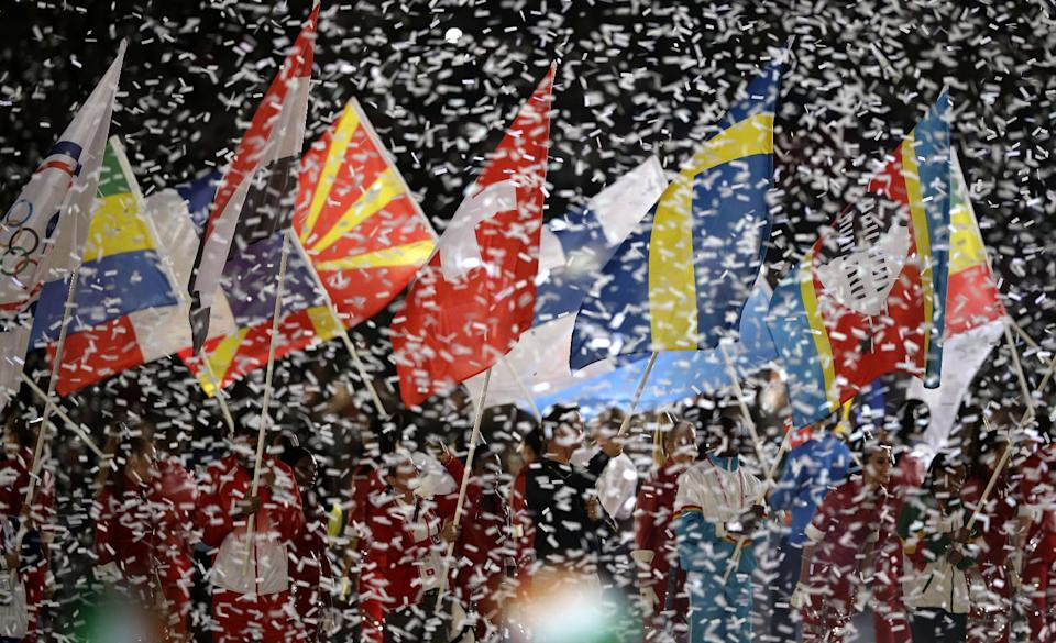 Confetti surrounds athletes waving their national flags during the Closing Ceremony at the 2012 Summer Olympics, Sunday, Aug. 12, 2012, in London. (AP Photo/Matt Slocum)