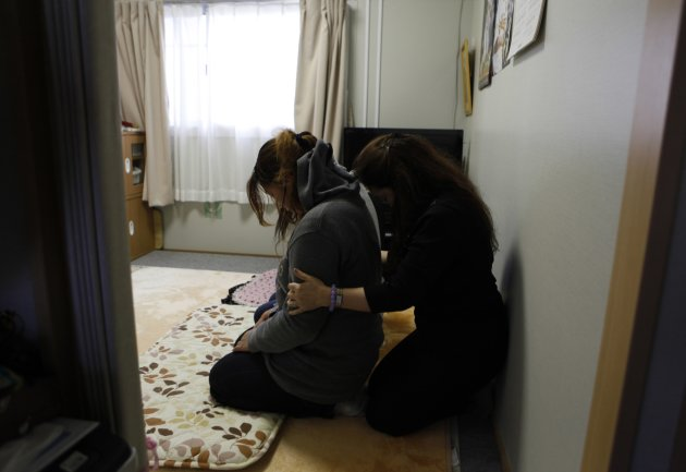 Fifty-six-year-old exorcist Kansho Aizawa (R) holds a spiritual cleansing ritual for a woman at a temporary house in Higashimatsushima, Miyagi prefecture, February 21, 2013, ahead of the second-year anniversary of the March 11, 2011 earthquake and tsunami. The tsunami that engulfed northeastern Japan two years ago has left some survivors believing they are seeing ghosts. In a society wary of admitting to mental problems, many are turning to exorcists for help. Picture taken February 21, 2013. REUTERS/Chris Meyers (JAPAN - Tags: DISASTER)