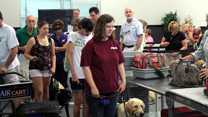 In this July 14, 2012, photo provided by Air Hollywood, members and volunteers from Guide Dogs for the Blind, GDB, take a K9 flight class, as they wait in line at a mock TSA screening at the Air Hollywood K9 flight school in Los Angeles. The idea was the brainchild of Talaat Captan, president and CEO of Air Hollywood, the world's largest aviation-themed film studio, who noticed a dog owner having a rough go getting a pooch through airport security. (AP Photo/Air Hollywood, Matt Souder)