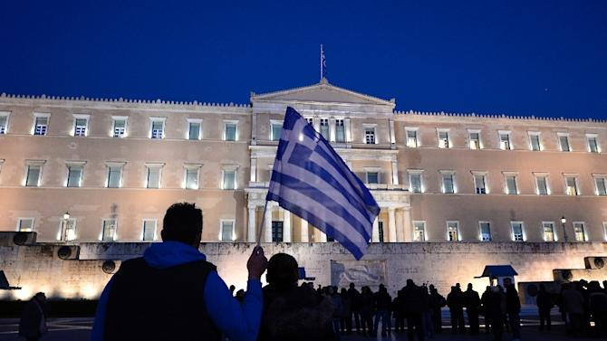 A man holds a Greek flag in front of the parliament in Athens as people gather in support to their government on February 20, 2015