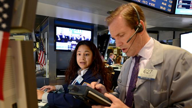 Wingszi Chang, left, of Getco Securities, and Michael Smyth of MND Partners trade on the floor of the New York Stock Exchange Monday, July 23, 2012 in New York. The Dow Jones industrial average closed down 101.11 points to 12721.46. (AP Photo/Henny Ray Abrams)