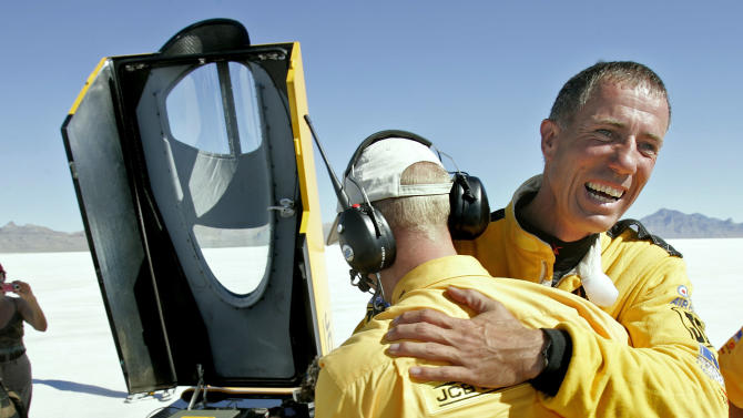 """FILE - This is a Tuesday, Aug. 22, 2006 file photo of British driver Andy Green, right, as he is congratulated by a crew member after setting a new unofficial world diesel powered land speed record of over 328 mph over two runs  on the Bonneville Salt Flats in Utah.. Toiling with shovels, wheelbarrows and bare hands, about 300 workers in a remote corner of South Africa removed 6,000 tons of stones and other debris _ roughly 20 tons per person _ from a vast stretch of desert over the past year. If all goes well, it will become the globe's fastest race track when a British-led team tries to break the world land-speed record in 2015.  """"It will be a brisk ride,"""" said Andy Green, the man who plans to break his own record. His goal this time? A flabbergasting 1,610 kilometers (1,000 miles) an hour. The track of hard-packed earth at the Hakskeen Pan, tucked between Namibia and Botswana, is 1.1 kilometers (0.7 miles) wide and 20 kilometers (12.5 miles) long.  (AP Photo/Douglas C. Pizac, File)"""