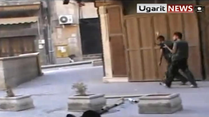 In this image taken from video obtained from Ugarit news, which has been authenticated based on its contents and other AP reporting, Syrian rebels prepare to throw hand grenades at government forces in Aleppo, Syria, Friday, Sept. 28,2012. Syrian rebels and residents of Aleppo struggled Saturday to contain a huge fire that destroyed parts of the city's medieval souks, or markets, following raging battles between government troops and opposition fighters there, activists said. Some described the overnight blaze as the worst blow yet to a historic district that helped make the heart of Aleppo, Syria's largest city and commercial hub, a UNESCO world heritage site. (AP Photo/Ugarit News via AP video)