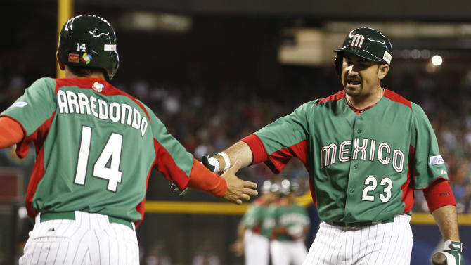 Mexico's Adrian Gonzalez, right, congratulates Eduardo Arredondo (14) after Arredondo scores a run against the United States in the first inning during a World Baseball Classic baseball game on Friday, March 8, 2013, in Phoenix. (AP Photo/Ross D. Franklin)