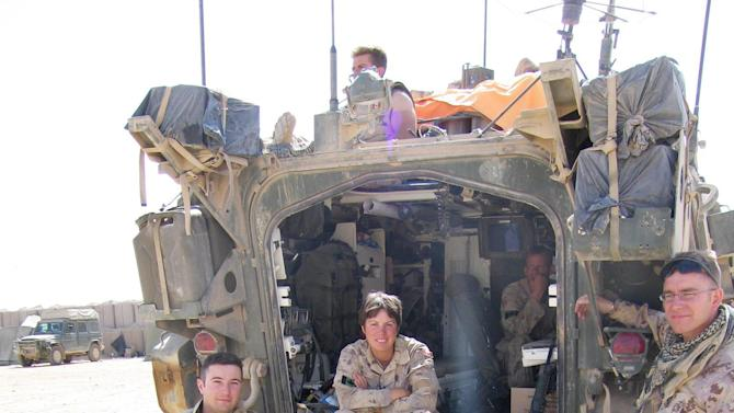 This April 16, 2006 photo shows, from left, Canadian Armed Forces Lt. Bryan Fleming, Capt. Nichola Goddard, and Capt. Mark Peebles, on the back of a military vehicle on Easter Sunday at Forward Base Robinson near Sangin, Afghanistan in Helmand province. Goddard, of 1st Royal Canadian Horse Artillery, was killed in action on May 17, 2006 near Kandahar, Afghanistan. (AP Photo/The Canadian Press, Murray Brewster)