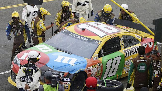 Kyle Busch has his car worked on in the pits after an accident during the NASCAR Sprint Cup series auto race on Sunday, June 23, 2013, in Sonoma, Calif. (AP Photo/Ben Margot)