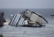 The Costa Concordia ship lies on its side on the Tuscan Island of Giglio, Italy, early Monday, Sept. 16, 2013. In an unprecedented maritime salvage operation, engineers on Monday gingerly wrestled the hull of the shipwrecked Costa Concordia off the Italian reef where the cruise ship has been stuck since January 2012. But progress was much slower than predicted and the delicate operation to rotate the luxury liner from its capsized position to upright appeared likely to stretch into Tuesday. Never before has such an enormous cruise ship been righted, and the crippled Concordia didn't budge for the first three hours after the operation began, engineer Sergio Girotto told reporters. (AP Photo/Andrew Medichini)