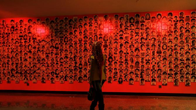 In this Tuesday, March 5, 2013 photo, an Iraqi woman looks at a display of pictures of people killed by Saddam Hussein's regime at the Shaheed Monument in Baghdad, Iraq. Saddam Hussein had the split teardrop-shaped sculpture built in the middle of a manmade lake in the early 1980s to commemorate Iraqis killed in the Iran-Iraq War. The names of hundreds of thousands of fallen Iraqi soldiers are inscribed in simple Arabic script around the base. In recent years, the Shiite-led government has begun turning it into a museum honoring the overwhelmingly Shiite and Kurdish victims of Saddam's Sunni-dominated but largely secular regime. (AP Photo/Khalid Mohammed)