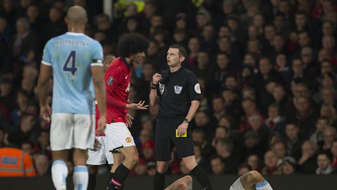 Manchester United's Marouane Fellaini, center left, reacts after receiving a yellow card from referee Michael Oliver for a challenge on Manchester City's Pablo Zabaleta, bottom, during their English Premier League soccer match at Old Trafford Stadium, Manchester, England, Tuesday, March 25, 2014