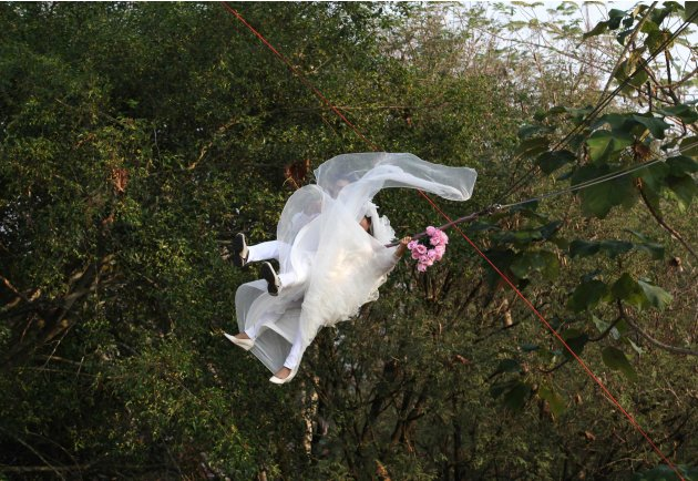 Thai groom Prasit Rangsiyawong and his bride Varuttaon Rangsiyawong fly while attached to cables during a wedding ceremony in Prachin Buri province