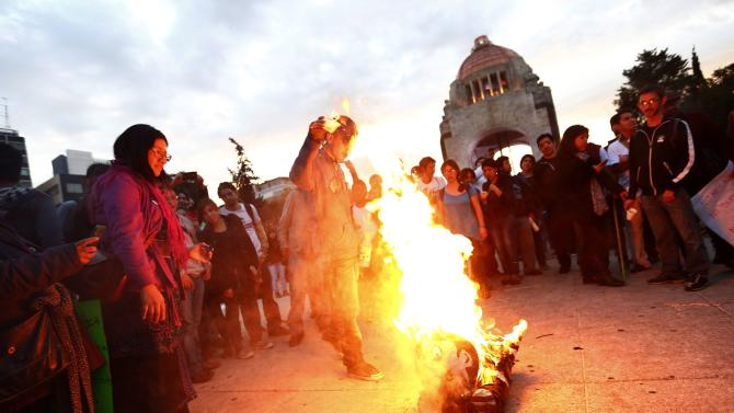 Activists burn a figure of President Enrique Pena Nieto during a march to demand justice for the 43 missing students from Ayotzinapa Teacher Training at Revolucion monument in Mexico City