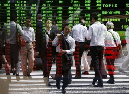 Passersby are reflected on a stock quotation board at a brokerage in Tokyo