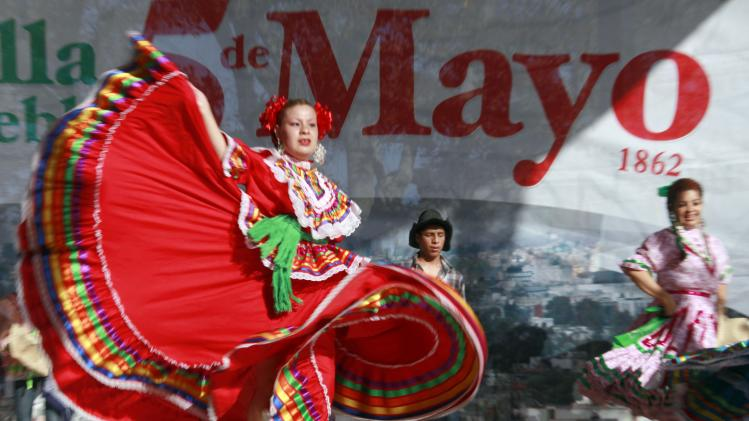 FILE - In this May 5, 2011 file photo, Marylin Castillo dances in honor of the Cinco de Mayo celebration in Los Angeles.  Cinco de Mayo has become in the U.S.: a celebration of all things Mexican, from mariachi music to sombreros, marked by schools, politicians and companies selling everything from beans to beer. (AP Photo/Nick Ut, file)