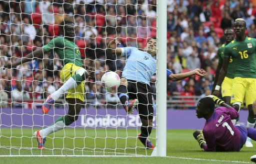 Uruguay's Luis Suarez fails to score against Senegal's Ousmane Mane blocked by Saliou Ciss during their men's preliminary first round Group A soccer match at the London 2012 Olympic Games in the Wembley Stadium in London