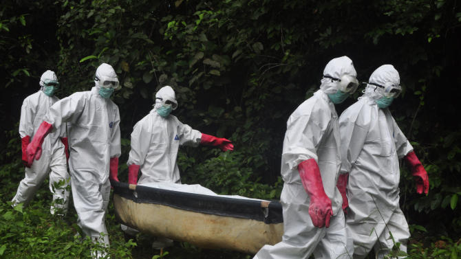 FILE - In this Saturday, Oct. 18, 2014 file photo, a burial team in protective gear carry the body of woman suspected to have died from the Ebola virus in Monrovia, Liberia. (AP Photo/Abbas Dulleh, File)