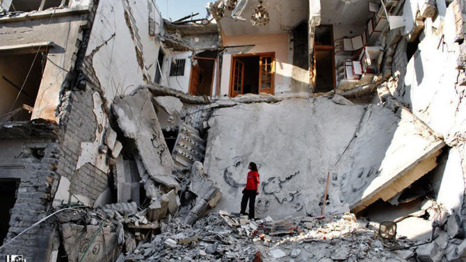 File-This file photo released on Thursday, June 27, 2013 by the anti-government activist group Lens Young Homsi, which has been authenticated based on its contents and other AP reporting, a Syrian stands in the rubble of a destroyed buildings from Syrian forces shelling, in the al-Hamidiyyeh neighborhood of Homs province, Syria. Rebels make their last stand in Homs, fighting desperately to cling to their last bastion in the city's old quarters as emboldened forces loyal to President Bashar Assad launch a fierce assault to evict them completely from the city once known as the capital of the revolution. (AP Photo/Lens Young Homsi, File)