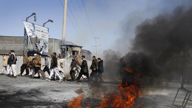 Afghans walk past tyres that were burnt by protesters during an anti-U.S. demonstration in Kabul, Afghanistan, Wednesday, Feb. 22, 2012. Anti-American demonstrations erupted on the outskirts of Kabul for a second day Wednesday and in another Afghan city over an incident that the U.S. said was inadvertent burning of Muslim holy books at a military base in Afghanistan. (AP Photo/Ahmad Jamshid)