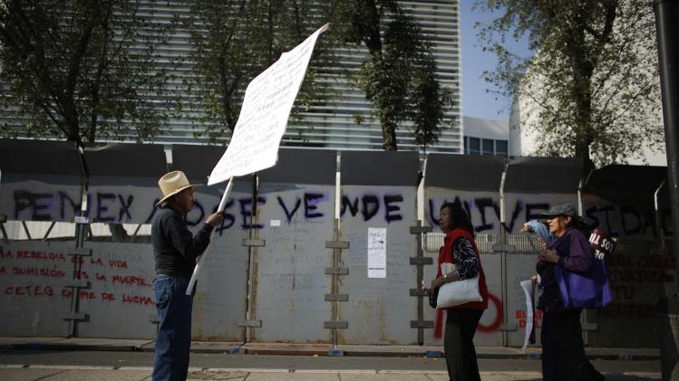 A demonstrator holds up a sign for passerbys to read as he protests against an energy reform bill outside the Senate building in Mexico City