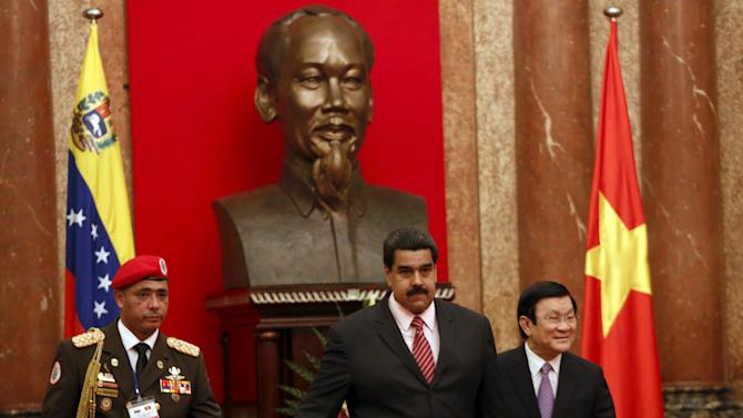Venezuela's President Nicolas Maduro walks with his Vietnamese counterpart Truong Tan Sang next to a Venezuelan military officer to the meeting room at the Presidential Palace in Hanoi, Vietnam