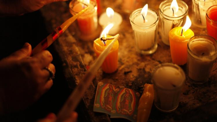 Pilgrims light candles next to images of the Virgin of Guadalupe in San Salvador