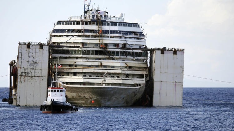 A rowing boat sails in front of the wreckage of the Costa Concordia cruise ship, almost ready to be towed away from the tiny Tuscan island of Isola del Giglio, Italy, Tuesday, July 22, 2014. The wreck of the Costa Concordia is expected to be towed to the Italian port of Genoa on Wednesday, where it will be scrapped. 32 people died when it slammed into the reef and started capsizing on Jan. 13, 2012. The body of one victim is still missing. (AP Photo/Gregorio Borgia)