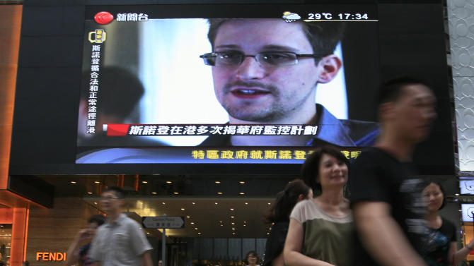 "A TV screen shows a news report of Edward Snowden, a former CIA employee who leaked top-secret documents about sweeping U.S. surveillance programs, at a shopping mall in Hong Kong Sunday, June 23, 2013. The former National Security Agency contractor wanted by the United States for revealing two highly classified surveillance programs has been allowed to leave for a ""third country"" because a U.S. extradition request did not fully comply with Hong Kong law, the territory's government said Sunday. (AP Photo/Vincent Yu)"