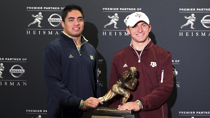 Notre Dame linebacker Manti Te'o, left, and Texas A&M quarterback Johnny Manziel, two of the three Heisman Trophy finalists, pose with the Heisman Trophy during a media availability, Friday, Dec. 7, 2012 in New York. Kansas State quarterback Collin Klein is the other finalist. (AP Photo/Mary Altaffer)