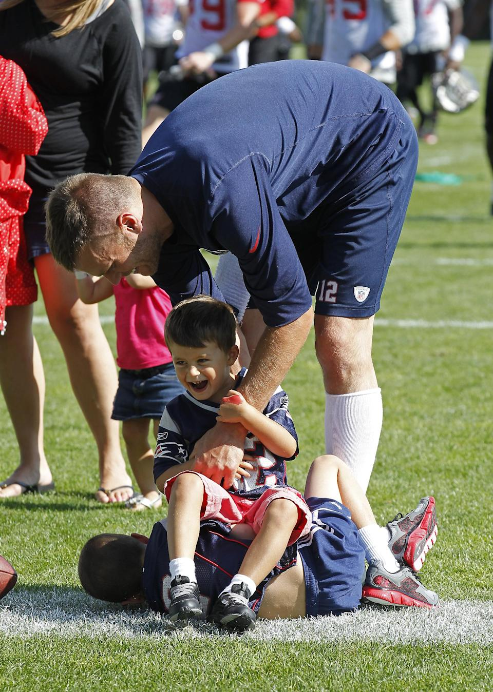 New England Patriots quarterback Tom Brady plays with his sons, John, on ground, and Benjamin, following the Patriots' joint workout with the Tampa Bay Buccaneers at NFL football training camp, in Foxborough, Mass., Thursday, Aug. 15, 2013. (AP Photo/Stew Milne)