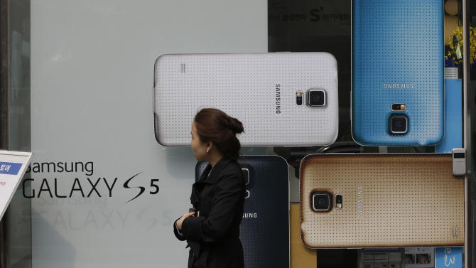 A woman walks by the advertisement of Samsung's Galaxy S5 smartphone at a mobile phone shop in Seoul, South Korea, Thursday, March 27, 2014. The global launch of Samsung's latest smartphone is being upstaged by South Korean mobile network companies. SK Telecom, South Korea's largest mobile carrier, said it will start selling the Galaxy S5 on Thursday, two weeks before the scheduled sales launch on April 11. (AP Photo/Lee Jin-man)